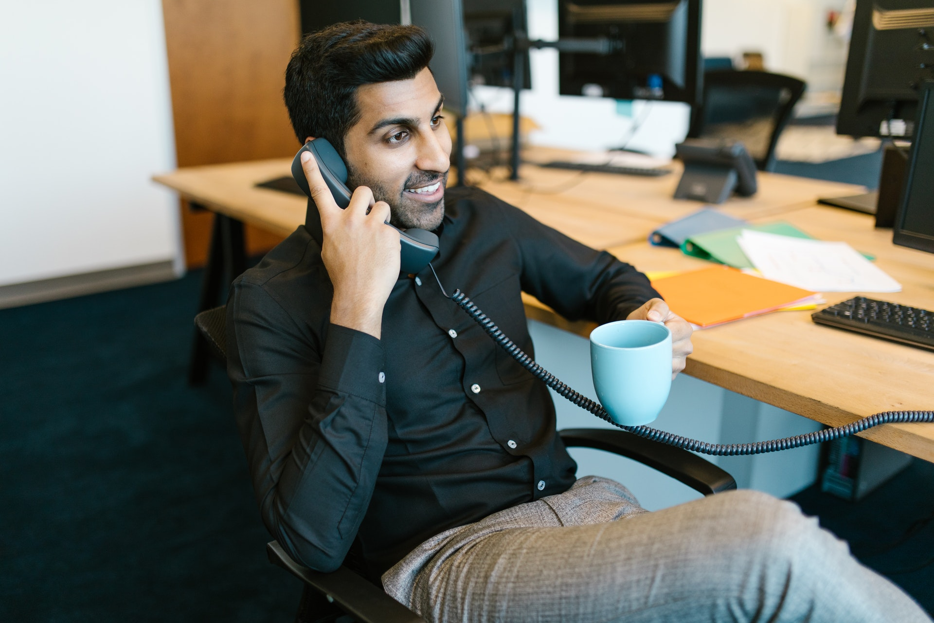 Man sitting in his office drinking coffee and talking on the phone, using a VoIP phone system