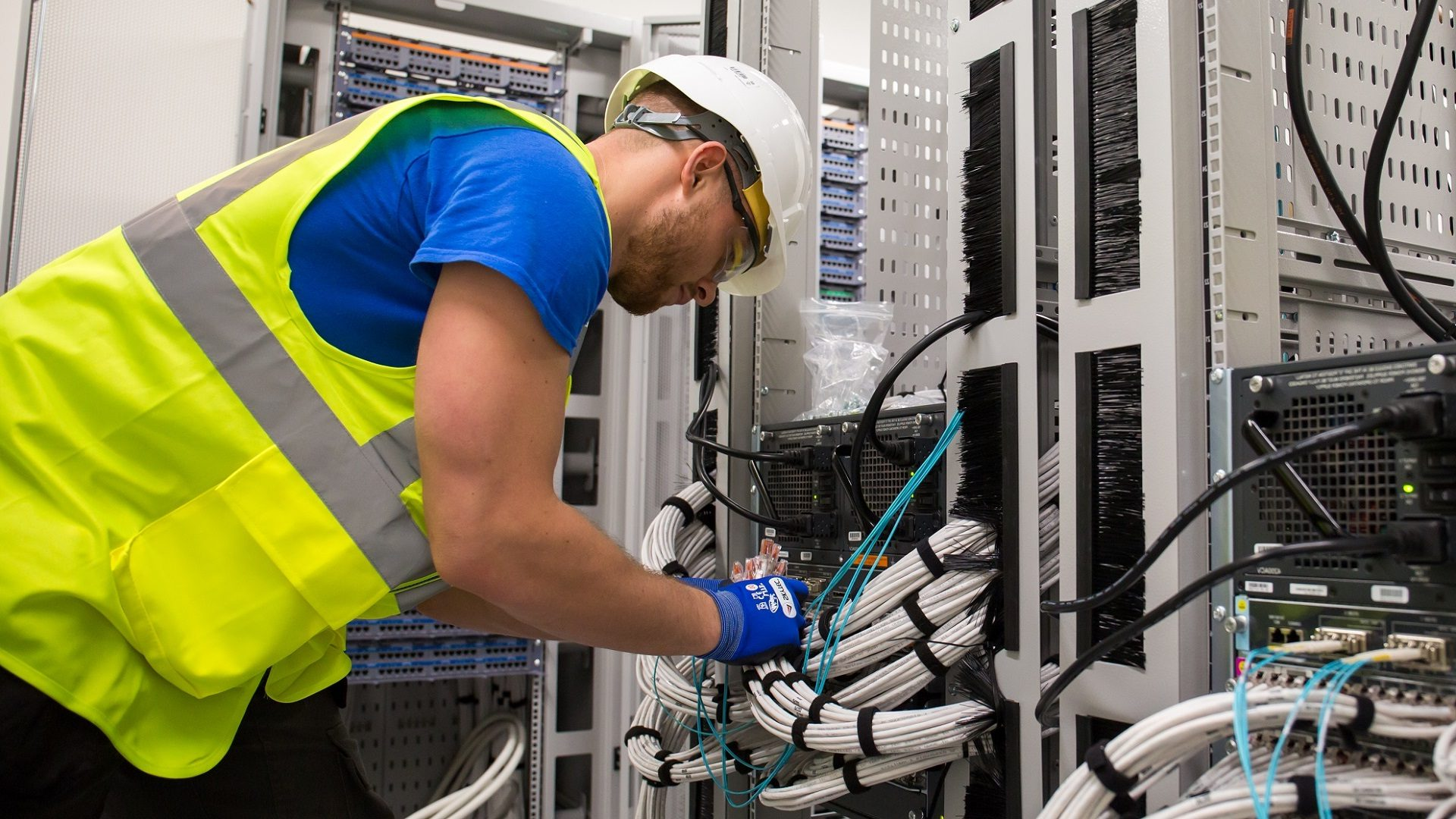 Man wearing high-visibility vest and hard hat installing networking cable in a commercial building.