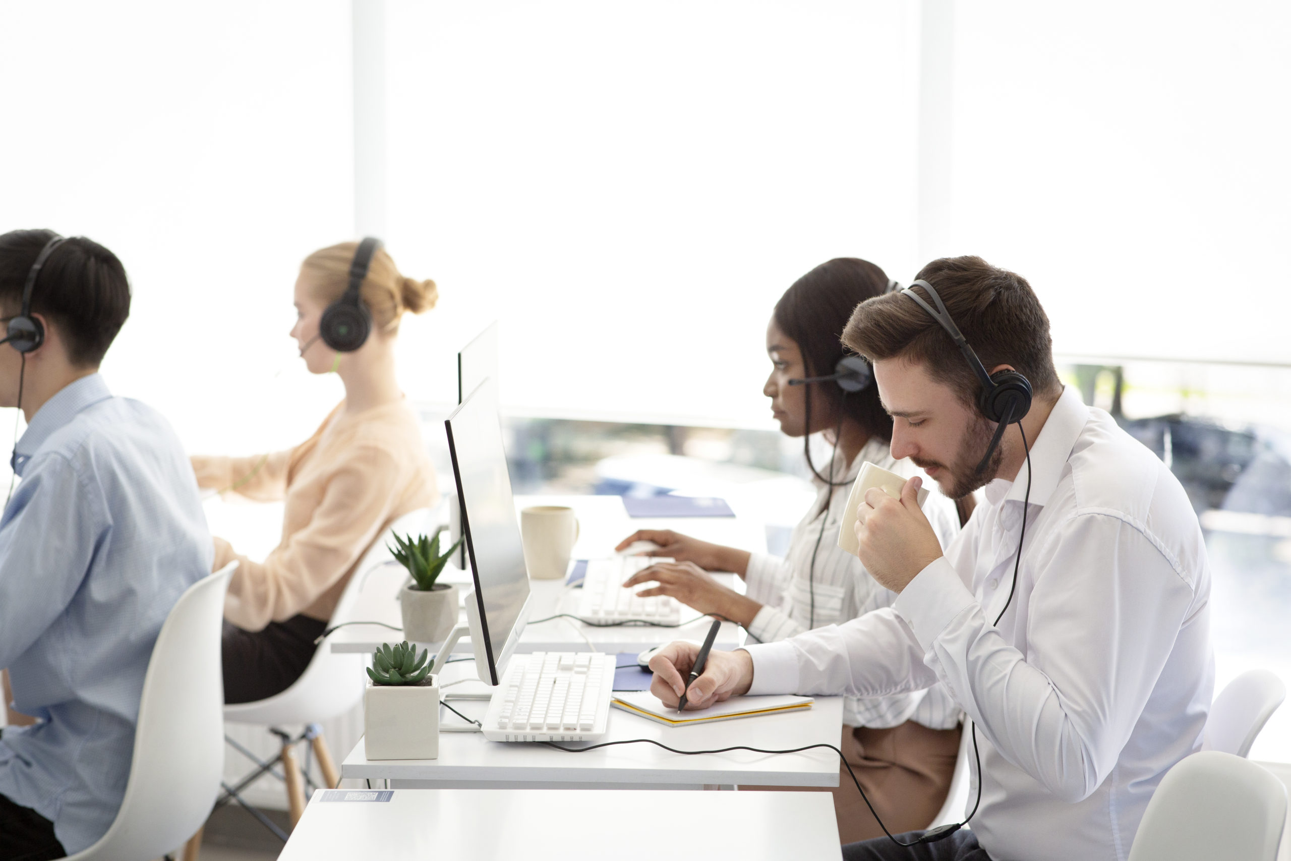 Multinational team of tech support operators at work at modern call centre office