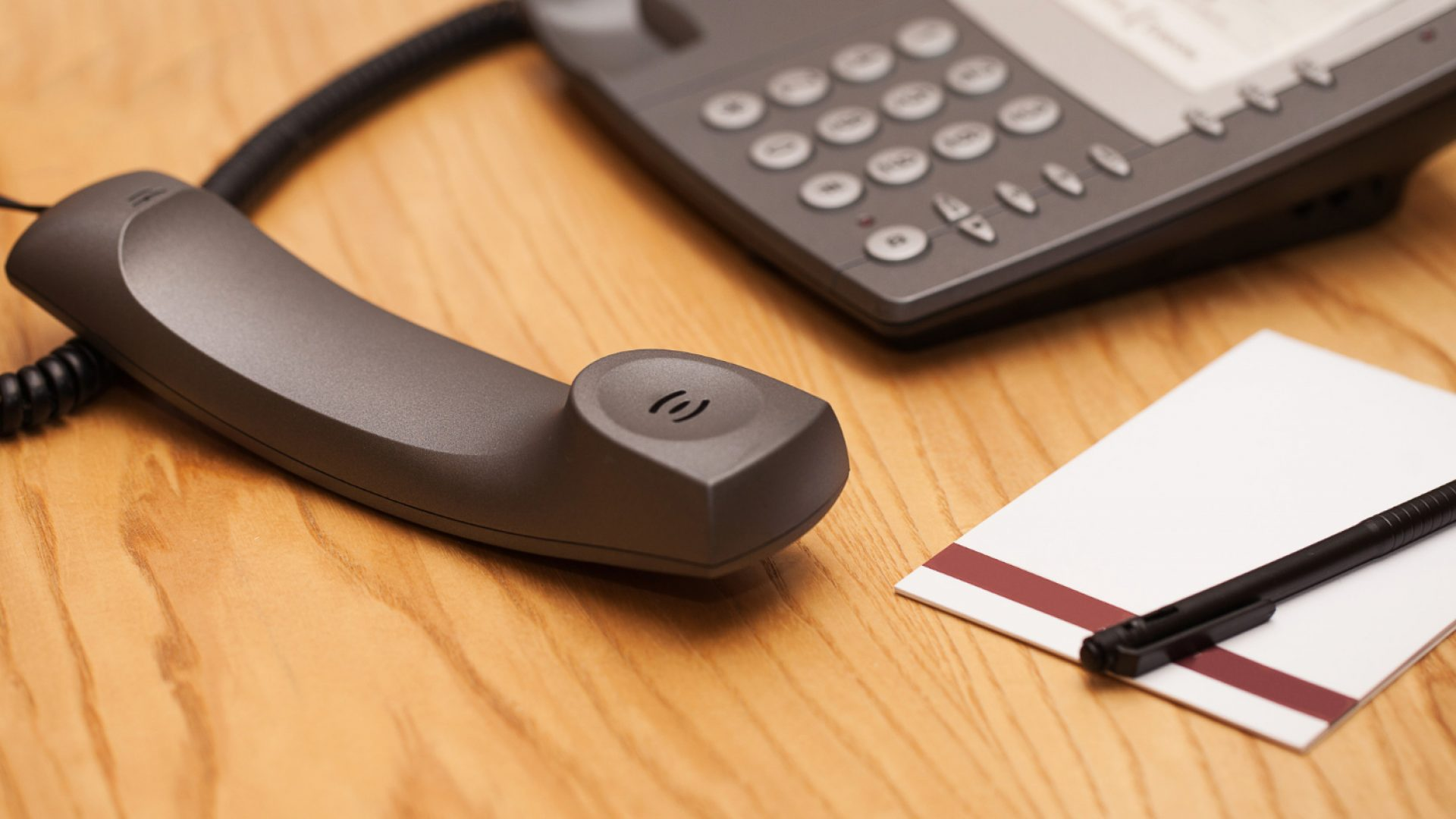 Close up of office desk phone with handset off-hook. Benefits of direct inward dialing